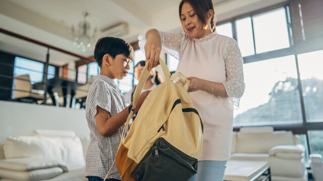 parent helping student with backpack