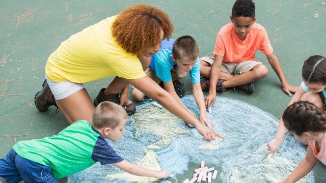 parent and neighborhood kids using sidewalk chalk