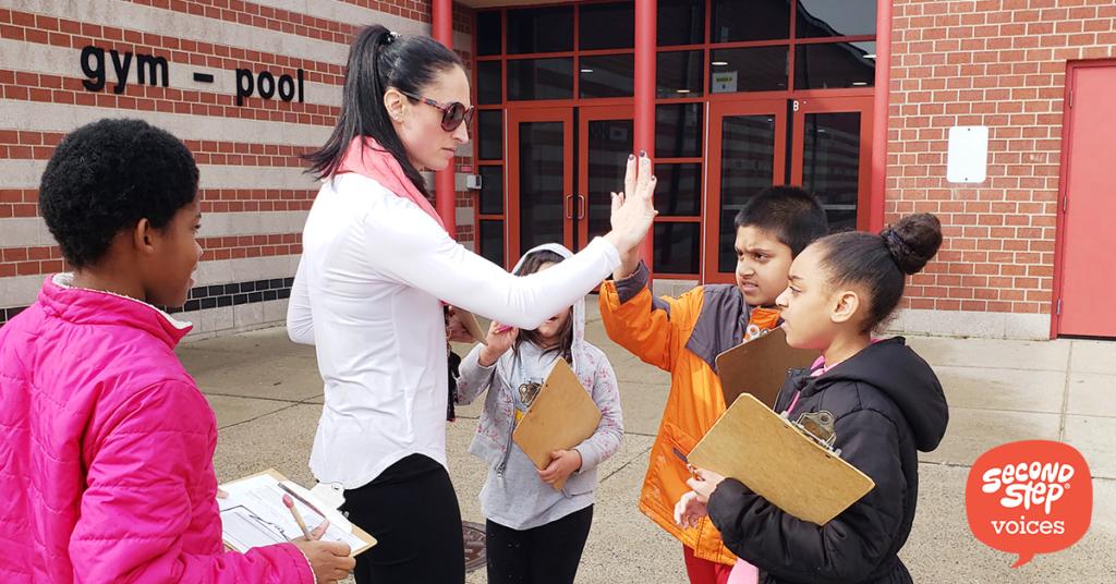 Teacher giving high-fives to kids